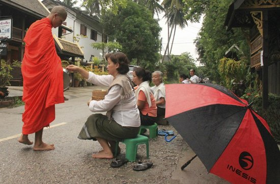 Villa Chitdara: Hotel owner and neighbour ladies giving food to the monks
