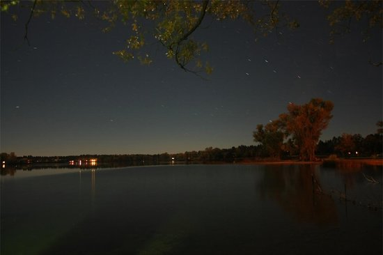 Rainbow Lake Resort: View from boathouse at night. Star trails of Sagittarius just above big tree on right.