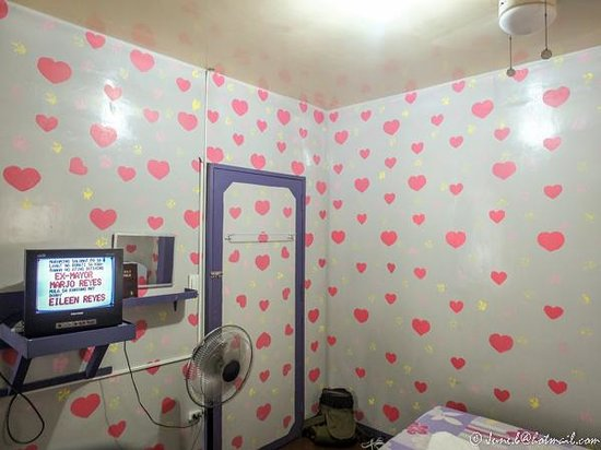 Mommita's Lodge: Pink hearts wall and TV, stand fan.