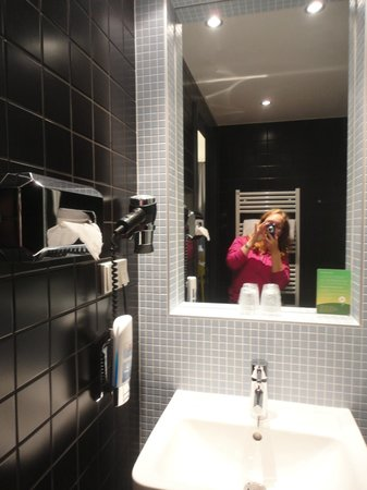 MEININGER Hotel Berlin Airport : big mirror and a hair dryer next to it.