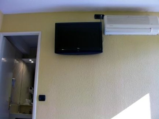 Hotel Le Mejean : Bedroom wall mounted TV, A/C & bathroom door take nearly all room size.