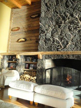Hotel Cumbres Puerto Varas: Sala da lareira revestida com lava vulcânica