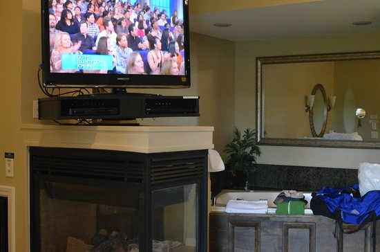 Belamere Suites: tv on top of fireplace in front of bed