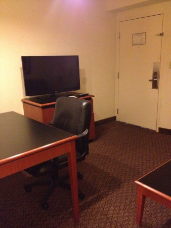Richmond Airport Hotel : Tv in the living room. Big leather chair for desk