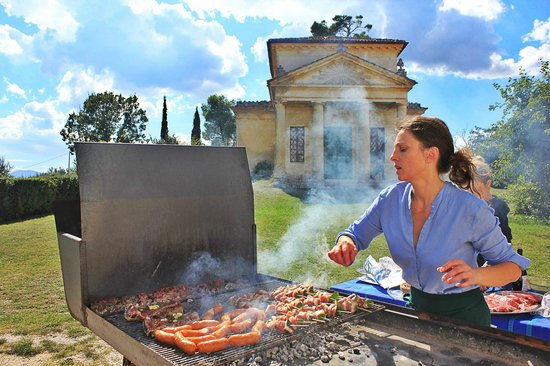 Villa Pianciani: Rita running the barbecue (converted agricultural plough)