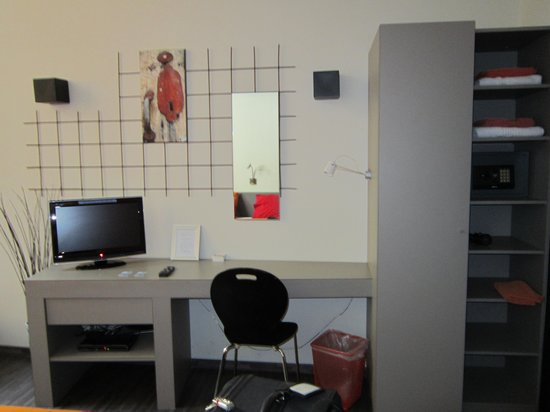 BXLROOM: In front of the bed, a small desk with the TV and the wardrobe with the safe