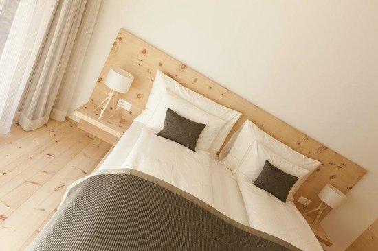 IN LAIN Hotel Cadonau: Schlafbereich in einer Garten-Suite