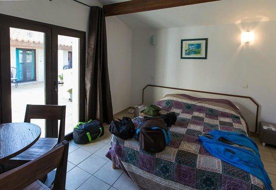 Le Maset : L'interno della camera con la porta finestra che da sulla corte comune