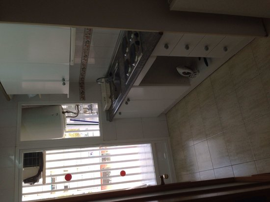 Benimar Apartments: Kitchen area leading to small area with a washing machine
