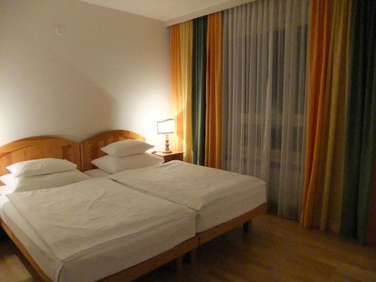 Hotel Caroline : Large windows with a privacy screen and curtains.