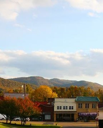 Elkton, VA: fall colors on the blue ridge mountains peek out behind a row of shops in elk tons town center.