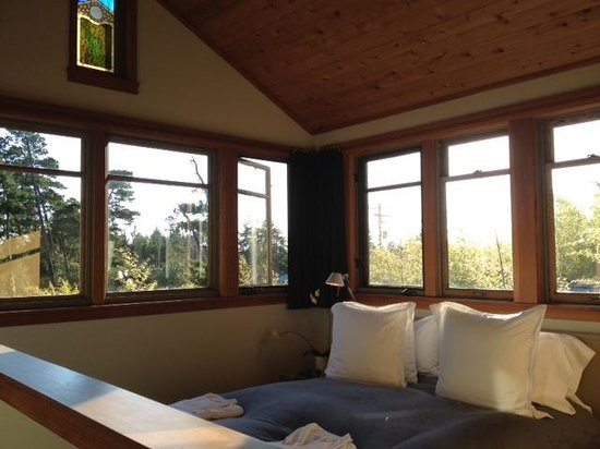Coast Cabins: Comfy bed with beautiful stained glass and windows