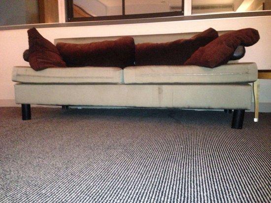 ONE UN New York: ONE, UN Hotel. New York, New York. Sofa: filthy, broken leg. Filthy carpet, filthy window, filth