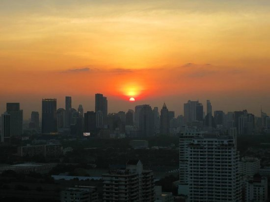 The Continent Hotel Bangkok by Compass Hospitality: sunset over BKK as seen from the pool