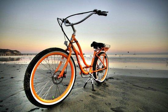 A Beautiful Orange Electric Pedego Bike On The Shore Near