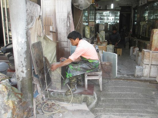 China Stone Carving City : Carver outside his store shaping stone