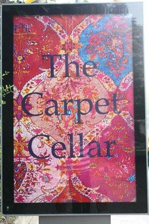The Carpet Cellar: the vibrant board outside