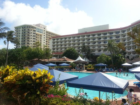 Hilton Guam Resort & Spa: 몇개의 수영장 중에 하나와 힐튼 호텔 건물