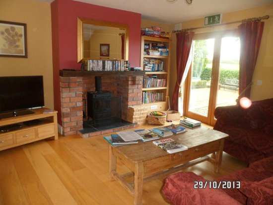 "Decoy Country Cottages : sitting room in ""The Den"" with game console, DVDs & library"