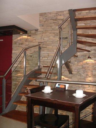 Aires de Tandil: el 1er piso: sector mesas para desayuno con una escalera al 2do piso