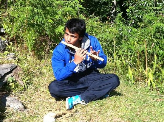 Asian Journey : Multi-talented guide, Manoj, playing the flute during a break on the trek