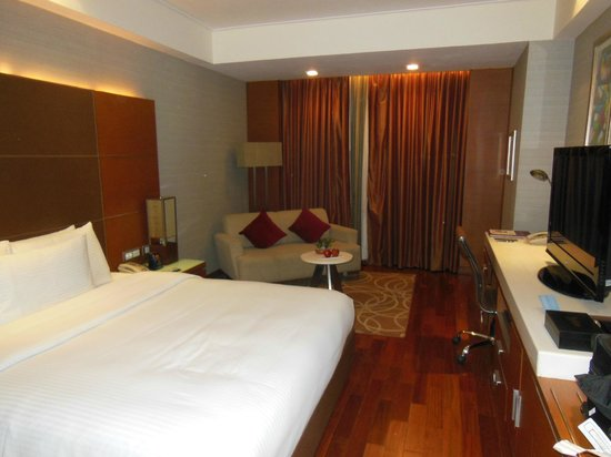 Piccadily Hotel New Delhi: The bed and sitting area in room 936