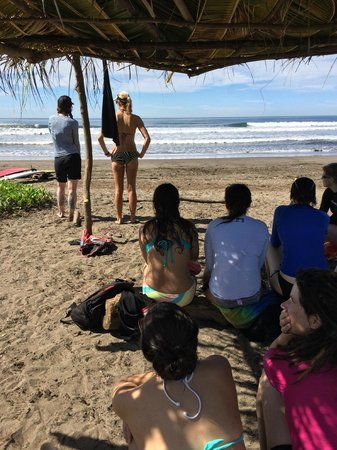 Surf With Amigas- Women's Surf and Yoga Retreat : checking out the waves under the shady beach palapa