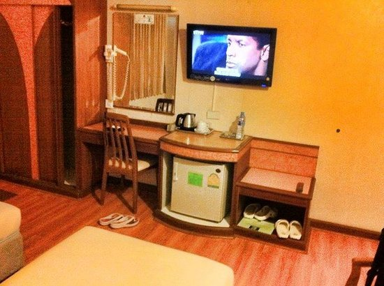 Sakol Hotel: the small mini bar/tv and vanity in the room