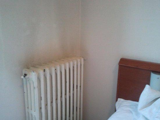 Hotel Paradiso: radiatore arrugginito e pareti nero-sporco