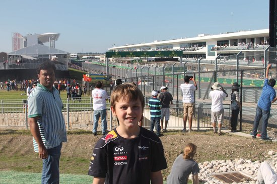 Circuit of The Americas: Brayden after several miles of walking.  Near tunnel # 1.  Front stretch in background
