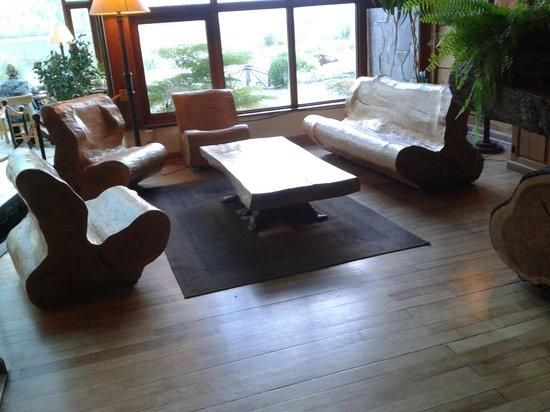 Hotel Natura Patagonia: Ambiente do estar com poltrona e sofá esculpidos em troncos de árvores nativas.