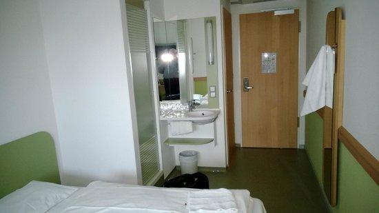 Ibis Budget Ulm City: Blick auf Dusche/Waschbecken, dahinter links die Tür zum WC