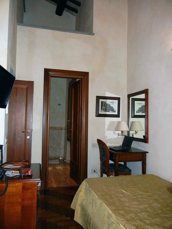 Hotel Teatro Pace: Bed, desk and, bathroom doorway; Entrance on left