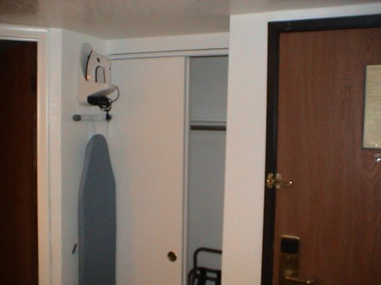 Airport Inn Hotel: Ironing Board, Iron, Closet, And Door To The Hallway