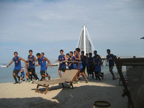 Los Muertos Pier: School boys jogging in the sand with the pier as a backdrop!