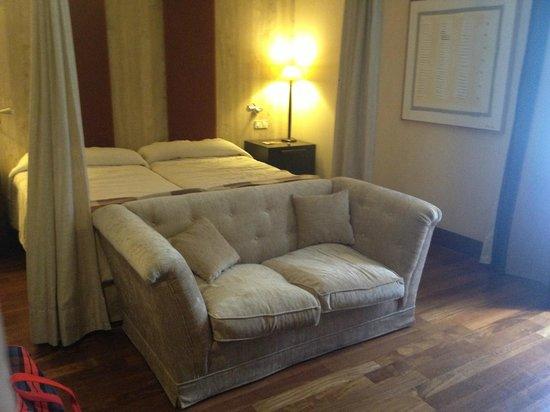 NH Collection Palacio de Burgos: cama con dosel y sofá a los pies