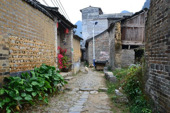 Jiuxian Ancient Village: Local resident in cobbled alleyways