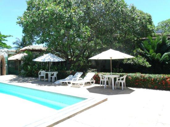 Hotel Quarup Praia : pileta y mesas con sombrillas