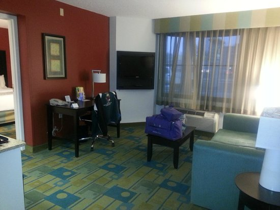 La Quinta Inn & Suites Milwaukee Bayshore Area: Living room area.  Includes sofa, coffee table, chair and desk with lots of outlets.