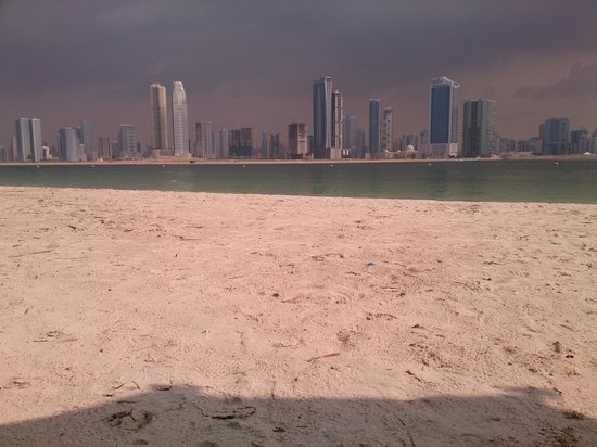 nice beach with the city backgrounds picture of al mamzar beach