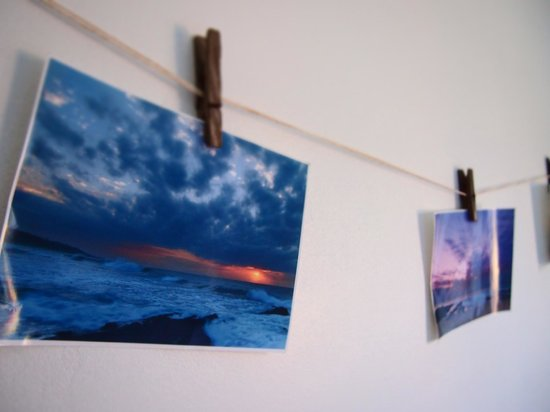 Umzumbe Surf House & Surf Camp: Seascape photos of Umzumbe Beach hang on a line in the Beach Break Room.