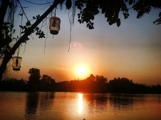 By de River: sunset of winter by the kwai yai river near river kwai bridge
