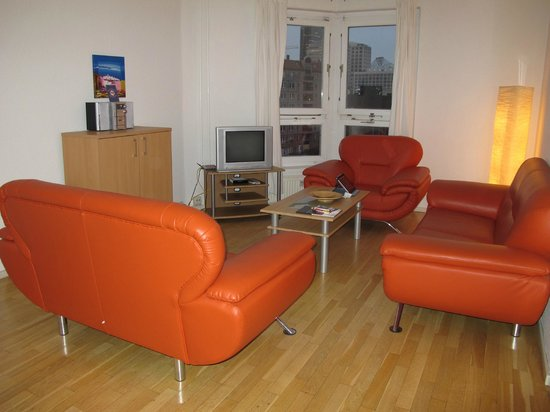 Apartments am Brandenburger Tor: Living room with orange couches