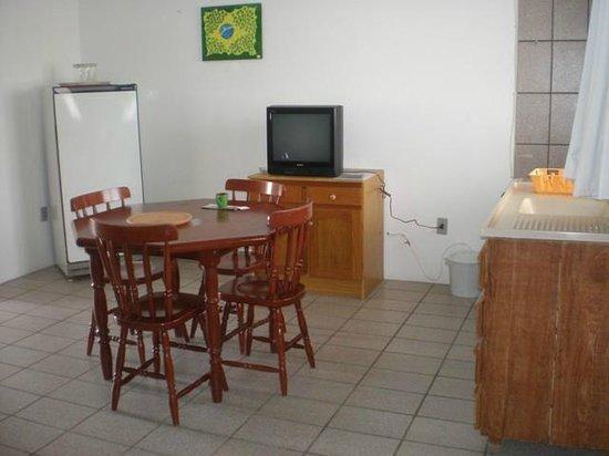 Residencial Mar & Dunas: Cozinha com fogão, geladeira, utensílios e TV cabo.