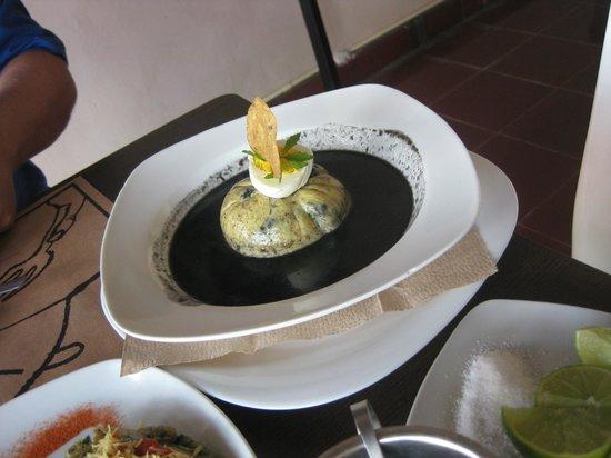 Manjar blanco : swiss cheese ball stuffed with mince and black bean mole sauce