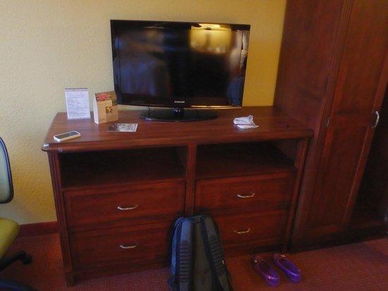 Rosen Inn: TV com as gavetas abaixo e o guarda-roupas logo ao lado