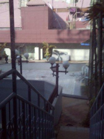 Hotel Horison Bekasi: Blick durch die verdunkelte Aussentüre auf den wasserlosen Pool inkl. Baugerüsten