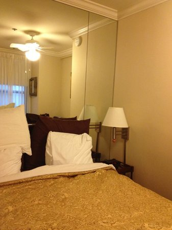 Inn at the Opera : Mirrored area behind bed --trying to make a small room bigger