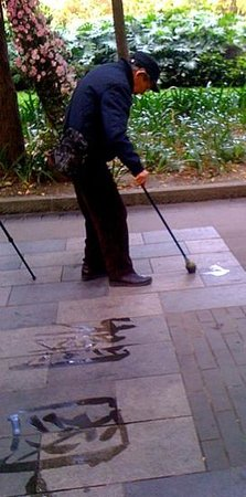 Huan Huaxi Park : man water paintscalligraphy on pavement stones in park ..Annh