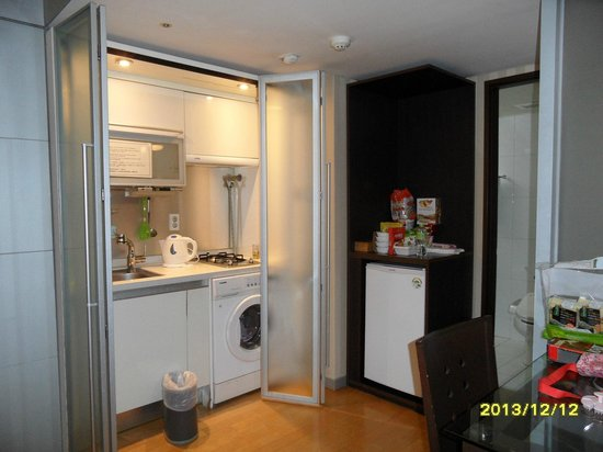 Provista Hotel: Kitchen with stove, refrigerator, and washer/dryer.